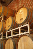 Wine barrels stacked in cellar area of vinery — Stock Photo