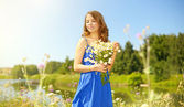 Beautiful girl with bunch of camomiles — Stock Photo