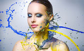 Beautiful girl and colorful paint splashes — Stock Photo