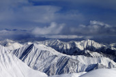 Sunlight snowy mountains and storm clouds — Stock Photo