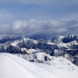 Off-piste snowy slope and mountains in cloud — Stock Photo #54125227