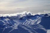 Des montagnes enneigées dans les nuages de brume et le soleil du soir — Photo