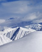 Top of off-piste snowy slope and cloud mountains — Stock Photo
