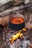 Borscht (Ukrainian soup) cooking on campfire — Stock Photo