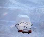 Snow-covered car with smiley in windshield — Stock Photo
