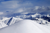 Top of off-piste snowy slope and cloudy mountains — Stock Photo