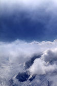 Snowy mountains in clouds and sunlight sky — Stock Photo