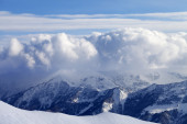 Snowy mountains in clouds and off-piste slope — Stock Photo