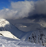 Off-piste slope and mountains with storm clouds — Stock Photo