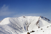 Off-piste slope with stones and snowy mountains — Foto Stock
