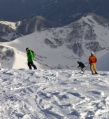 Snowboarders and skier on off-piste slope in sun evening — Stockfoto