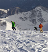 Snowboarders and skier on off-piste slope in sun evening — Foto Stock