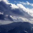 Helicopter in cloudy sky and winter mountains in evening — Stock Photo #60935445