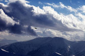 Helicopter in cloudy sky and winter mountains in evening — Stock Photo