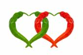 Red and green chili peppers in love — Stock Photo