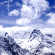 Snowy mountains in clouds at sun day — Stock Photo #73684039