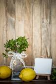 Mint in a glass vase, lemons and mini easel with blank canvas — 图库照片