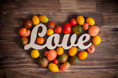 Love tomatoes on a brown wooden background — Stock Photo