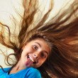Adorable child with longhair sticking her tongue out — Stock Photo #52831165