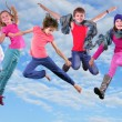 Happy children exercising and jumping in the blue sky — Stock Photo #55682751