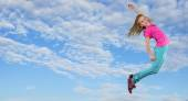 Little girl jumping and dancing against blue cloudy sky — Stock Photo