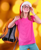 Child with Santa Claus red hat, backpack and glasses on bright background — Stock Photo