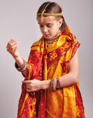Little girl putting on traditional Indian clothing and jeweleries — Stock Photo