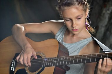 teenage girl playing guitar in the street