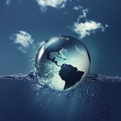 Earth globe on the water waves — Stock Photo