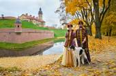 Couple in medieval costumes with borzoi dog — Stock Photo