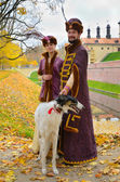 Couple in traditional medieval costumes with two borzoi dogs — Stock Photo