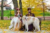 Couple in medieval costumes with borzoi dogs — Stock Photo