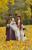Couple in medieval costumes with two borzoi dogs — Stock Photo