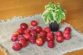 Plums scattered on the wooden table — Stock Photo