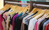 Variety of clothes hanging on rack in boutique — Stock Photo
