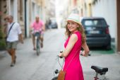 Preaty girl in hat and pink dress riding a bicycle — Стоковое фото