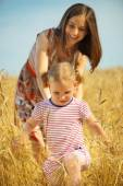 Young mother with little daughter at wheat field — Стоковое фото