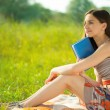 Beautiful young girl with book at wonderful green meadow — Stock Photo #56504267
