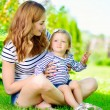 Young mother with little daughter in park — Stok fotoğraf #56747207
