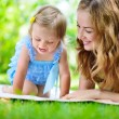 Young mother with little daughter reading book in park — Stok fotoğraf #56747259