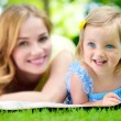 Young mother with little daughter reading book in park — Stok fotoğraf #56747301