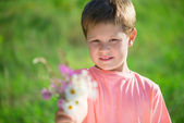 Cut little boy with bunch of flowers — Stock Photo