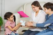 Mother and older brother presenting gift box to little sister on — Stock Photo