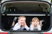 Little brother and sister in car boot — Foto Stock
