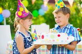Little girl giving a birthday cake to a friend — Stock Photo