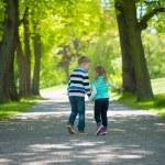 Two happy children walking in park — Stock Photo #75937695