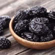 Prunes on a wooden background — Stock Photo #64891179