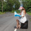 Girl sitting on a suitcase with a map — Stock Photo #53355419