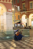 Harlequin with a guitar on street — Stockfoto