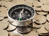 Compass on a heap of coins — Stock Photo